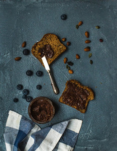 Whole grain bread toasts with organic vegan chocolate peanut butter  blueberry  nuts over grunge grey backdrop