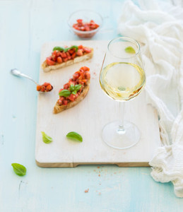 Glass of white wine  tomato and basil bruschetta sandwich on painted wooden serving board over rustic blue background