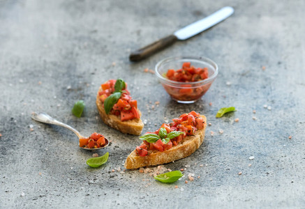 Tomato and basil bruschetta sandwich over grunge gray background