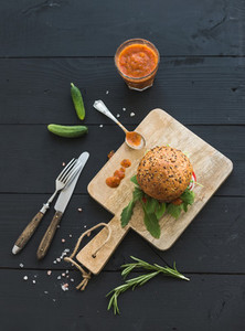 Fresh homemade burger on dark serving board with spicy tomato sa
