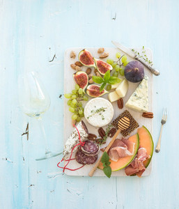 Wine and snack set Figs grapes nuts cheese variety meat appetizers herbs glass on light blue background top view