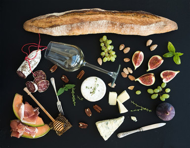 Wine and snack set Baguette glass of white figs grapes nuts cheese variety meat appetizers herbs on black grunge background top view