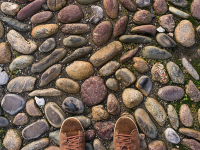 Feet in brown sneakers on the old medieval stone pavement