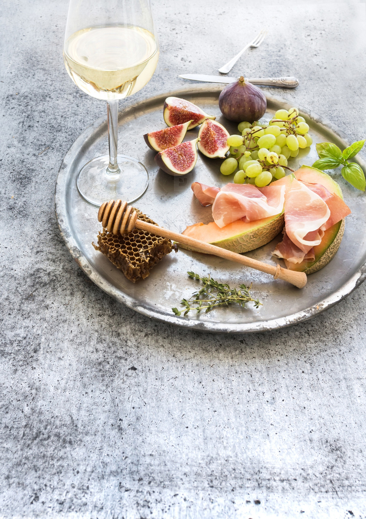 Wine appetizer set  Glass of white wine  honeycomb with drizzlier  figs  grapes  melon and prosciutto on silver tray over rustic grunge surface