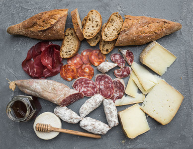 Cheese and meat appetizer selection or wine snack set  Variety of italian cheese  salami  bresaola  baguette  honey on over grey concrete backdrop  top view