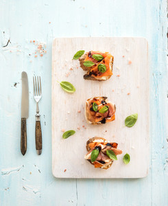 Bruschettas with Prosciutto  roasted melon  soft cheese and basil on wooden serving board over light blue background