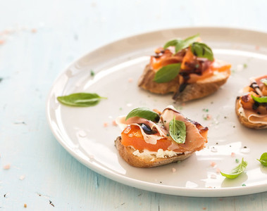 Bruschettas with Prosciutto roasted melon soft cheese and basil on white ceramic plate over light blue background
