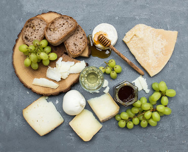 Cheese appetizer selection or wine snack set  Variety of italian cheese  green grapes  bread slices and honey on round wooden board over grey concrete backdrop  top view