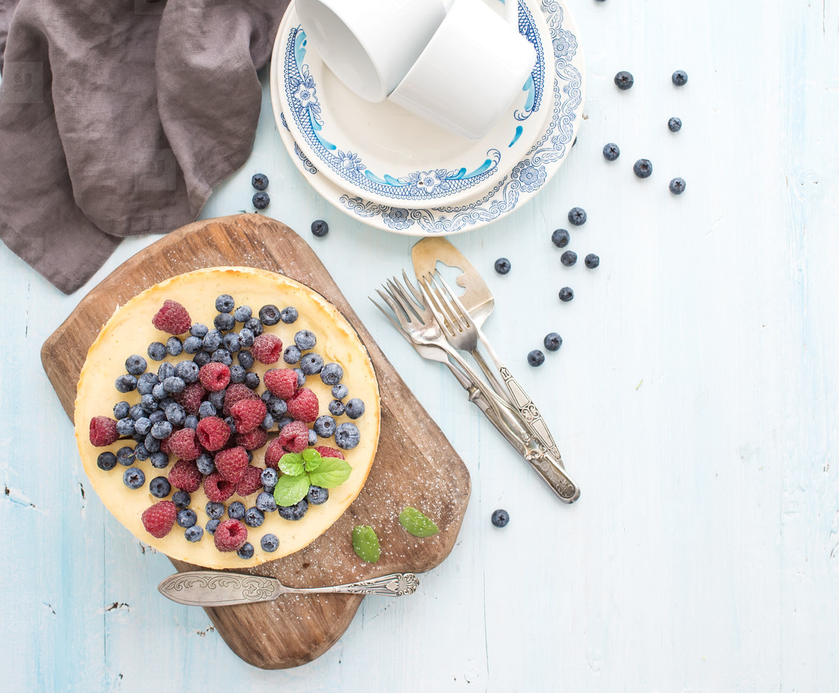 Cheesecake with fresh raspberries and blueberries on a wooden serving board  plates  cups  kitchen napkin  silverware over blue background