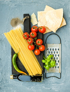 Ingredients for cooking pasta  Spaghetti  Parmesan cheese  cherry tomatoes  metal grater  olive oil and fresh basil on grey blue concrete background