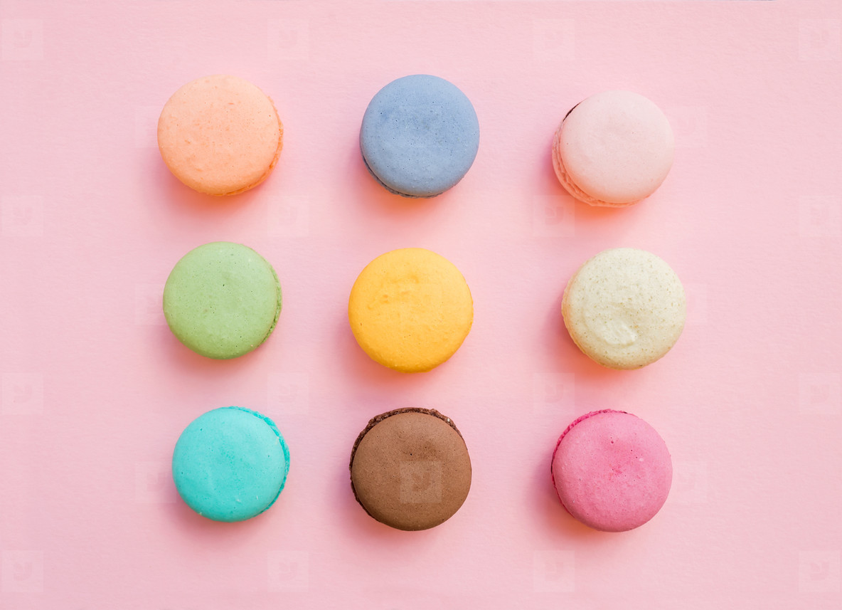 Sweet colorful French macaroon biscuits on pastel pink background