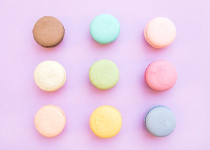 Sweet colorful French macaroon biscuits on pastel lilac background