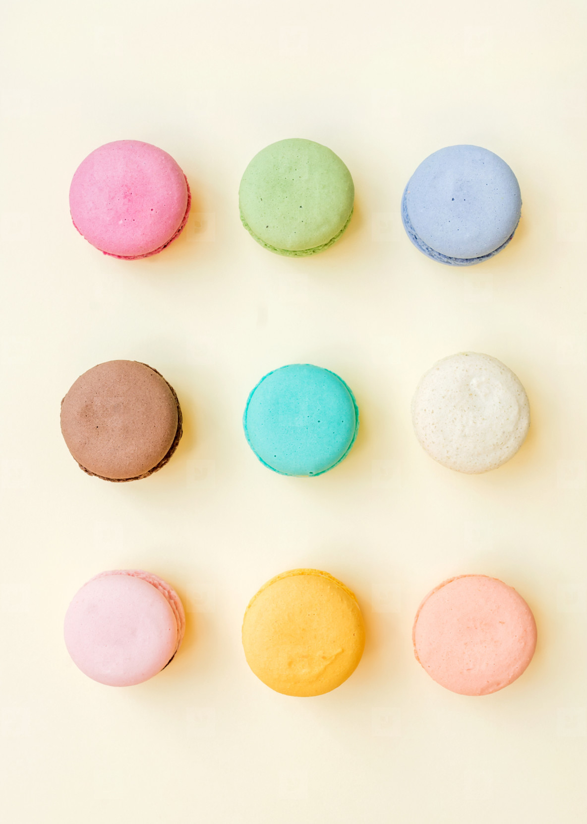 Sweet colorful French macaroon biscuits on pastel yellow background