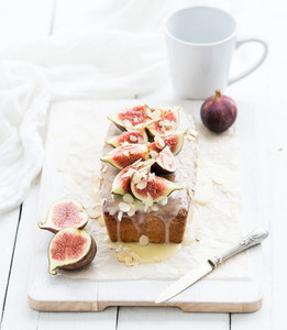Loaf cake with figs almond and white chocolate on wooden serving board over grunge background selective focus