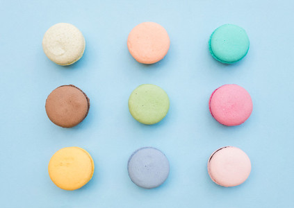 Sweet colorful French macaroon biscuits on pastel blue background