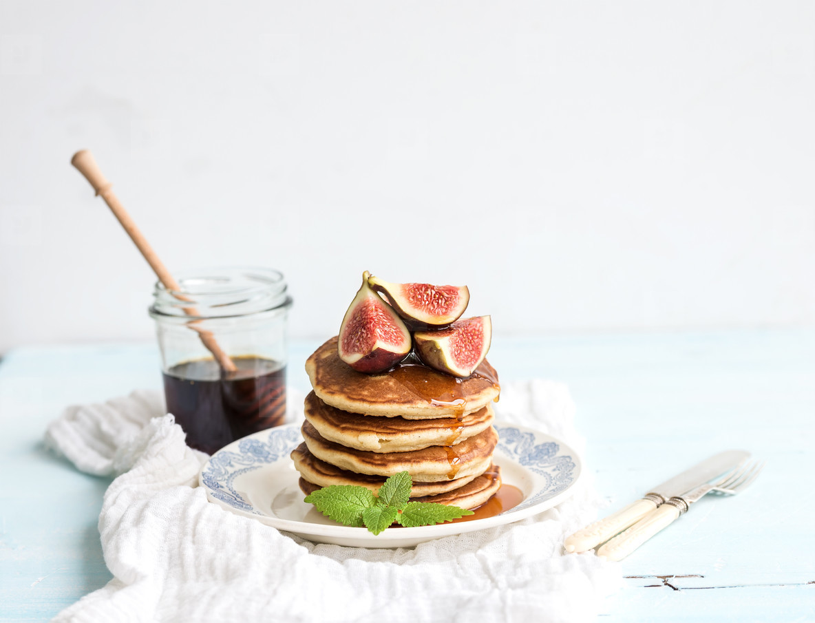 Pancake tower with fresh figs and honey on a rustic plate  White background