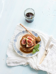 Pancake tower with fresh figs and honey on a rustic plate  Light blue  background