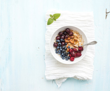 Healthy breakfast set  Bowl of oat porridge with fresh berries  almond and honey over white napkin  Top view  light blue backdrop