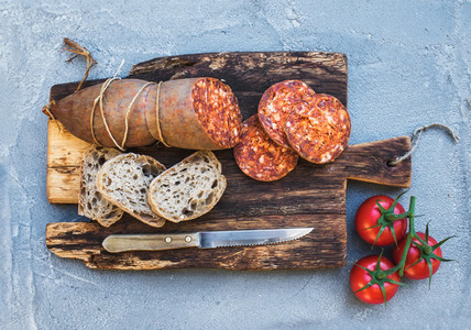 Wine snack set  Hungarian mangalica pork salami sausage  rustic bread and fresh tomatoes on dark wooden board over a rough grey blue concrete background