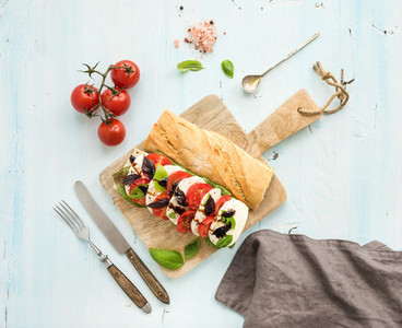 Tomato  mozzarella and basil sandwich on wooden chopping board over light blue background  top view