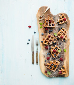 Soft Belgian waffles with berries  honey and mint on rustic wooden serving board over light blue background  top view