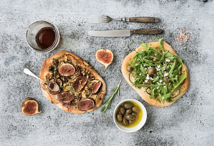 Rustic homemade pizzas with eggpant cheese olives arugula prosciutto and figs over grunge backdrop Top view