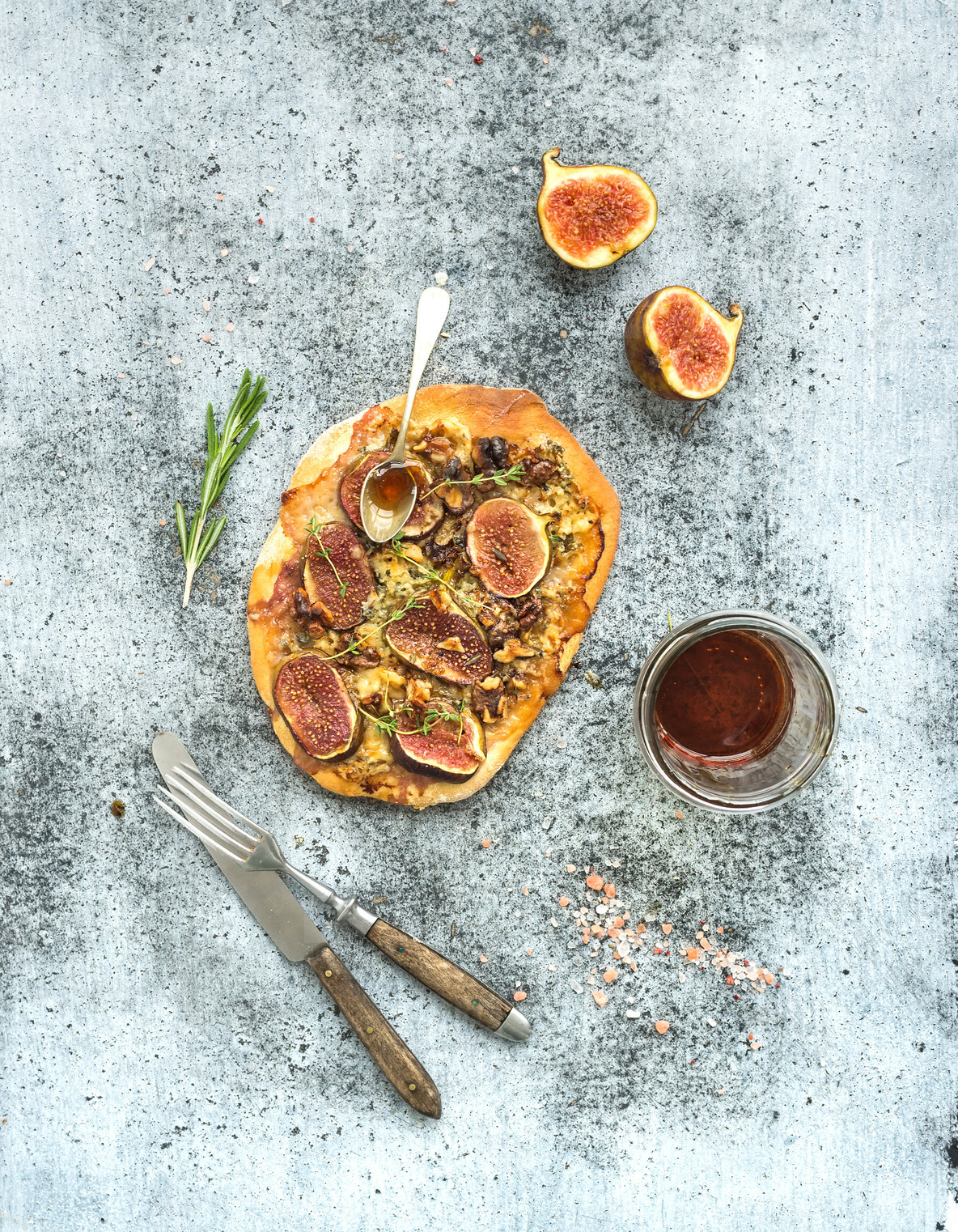 Rustic homemade pizza with figs  prosciutto and mozzarella cheese over grey grunge backdrop  Top view
