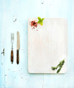 Kitchen ware set  White wooden chopping board  knife  fork  spices and herbs on a light blue background
