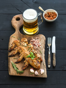 Fried chicken wings on rustic serving board spicy tomato sauce herbs and mug of light beer over black wooden backdrop