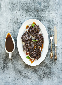 Chocolate Belgian waffles with salted caramel sauce and mint on white ceramic serving plate over grunge background top view