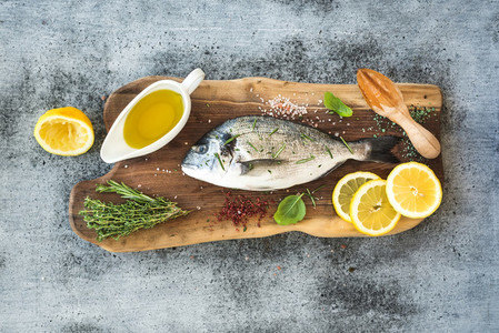 Fresh uncooked dorado or sea bream fish with lemon herbs oil and spices on rustic wooden board over grunge backdrop
