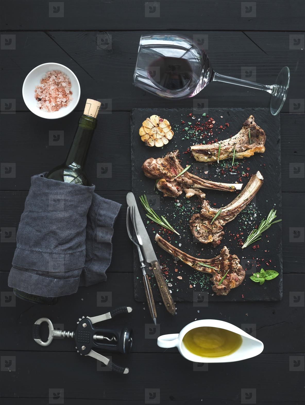 Grilled lamb chops  Rack of Lamb with garlic  rosemary  spices on slate tray  wine glass  oil in a saucer and bottle over black wood background