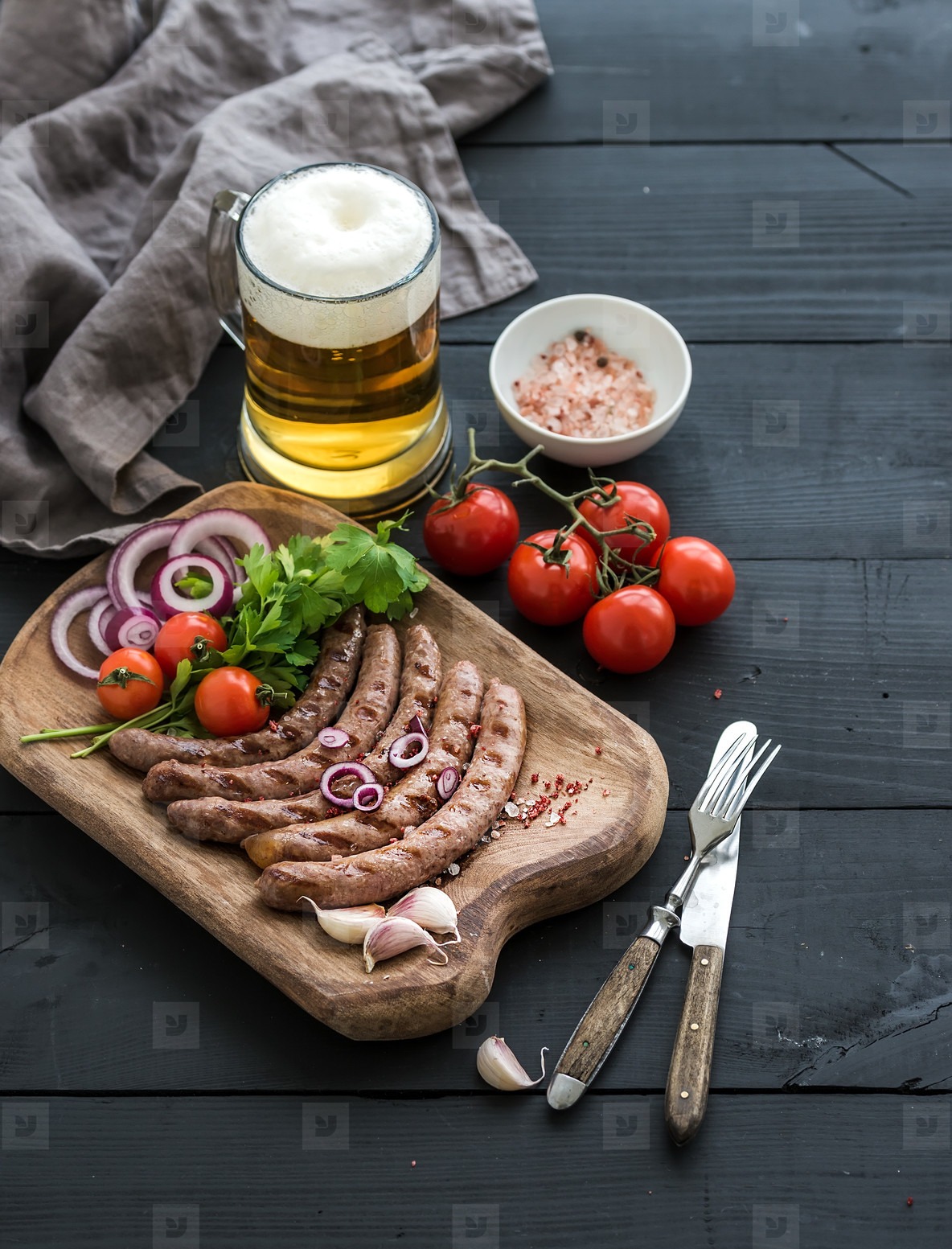 Grilled sausages with vegetables on rustic serving board and mug of light beer over black wooden backdrop
