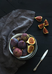 Rustic metal bowl of fresh figs on dark background top view selective focus