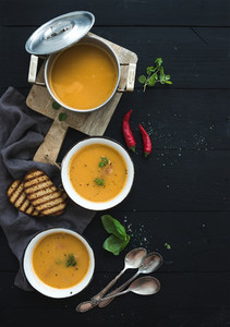 Red lentil soup with spices  herbs  bread in a rustic metal saucepan and bowls  over dark wood backdrop  top view