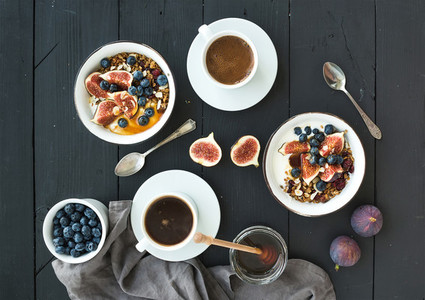 Healthy breakfast set  Bowls of oat granola with yogurt  fresh blueberries and figs  coffee  honey  over black wooden backdrop