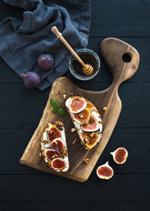 Sandwiches with ricotta  fresh figs  walnuts and honey on rustic wooden board over black backdrop