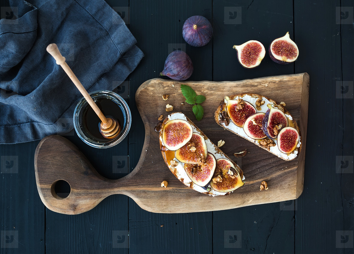 Sandwiches with ricotta  fresh figs  walnuts and honey on rustic wooden board
