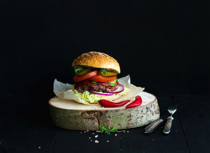 Fresh homemade burger on wooden serving board with spicy tomato sauce  sea salt and herbs over black  background