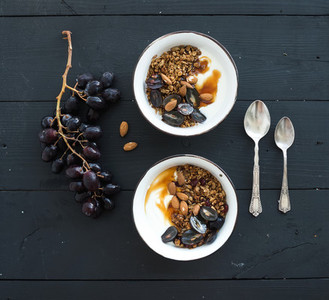 Healthy breakfast set  Bowls of oat granola with yogurt  fresh grapes  almond and  honey over black wooden backdrop