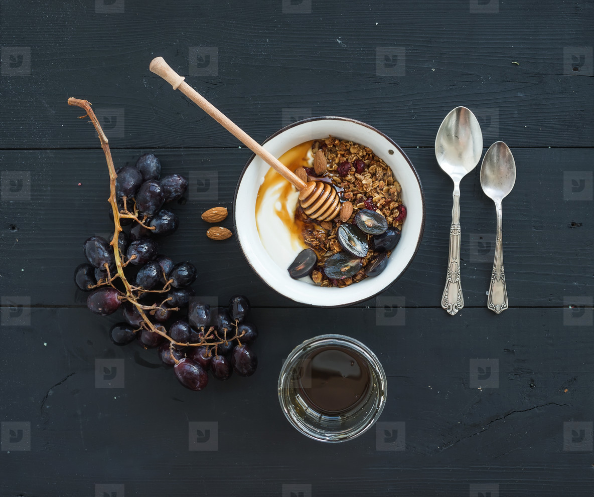 Healthy breakfast set  Bowl of oat granola with yogurt  fresh grapes  almond and  honey over black wooden backdrop