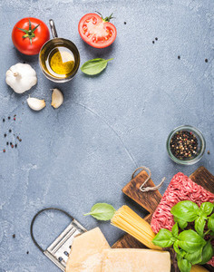 Ingredients for cooking pasta Bolognese  Spaghetti  Parmesan cheese   tomatoes  metal grater  olive oil  garlic  minced meat and fresh basil on grey concrete background  top view