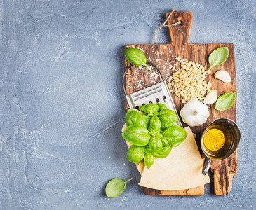 Ingredients for cooking Pesto sauce Parmesan cheese metal grater fresh basil olive oil garlic and pine nuts on old rustic wooden board over grey concrete background
