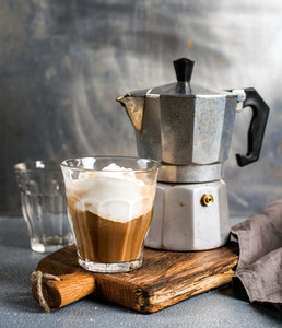 Glass of coffee with ice cream on rustic wooden board and steel Italian Moka pot