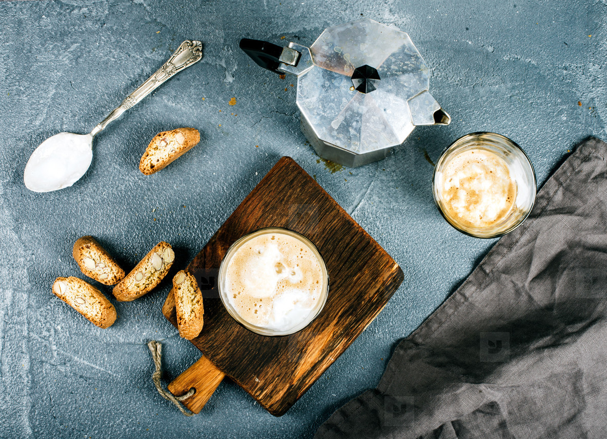 Glasses of coffee with ice cream on rustic wooden board  steel Italian Moka pot over grey concrete textured background