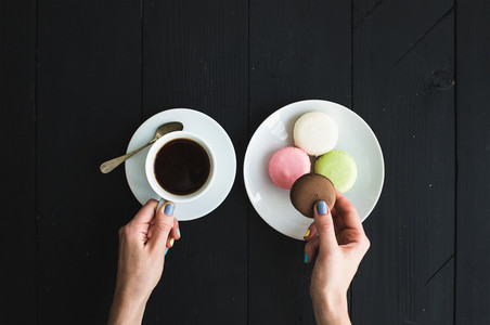Macaron cookies cup of espresso and ladies hands over black wooden backdrop