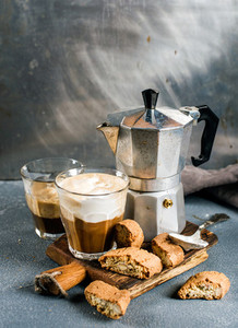 Glass of latte coffee on rustic wooden board  cantucci biscuits and steel Italian Moka pot  grey background