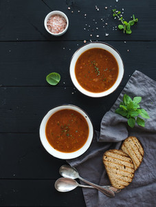 Roasted tomato soup with fresh basil  spices and bread in rustic metal bowls over black background