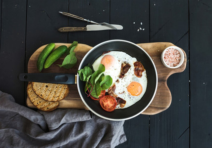 Pan of fried eggs  bacon  tomatoes with bread  mangold and cucumbers on rustic wooden serving board over dark table surface