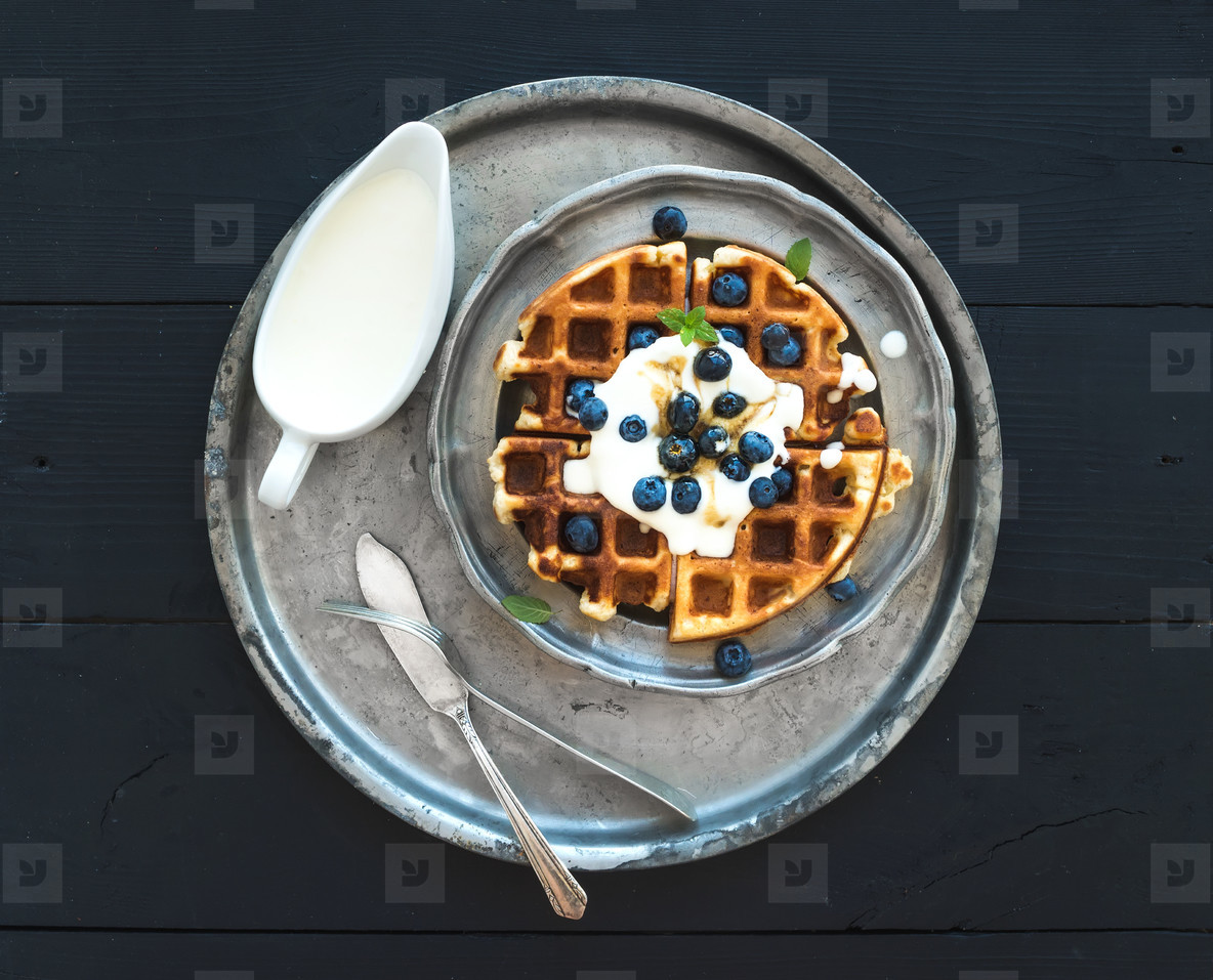 Soft Belgian waffles with blueberries  honey and whipped cream on vintage metal plate over black wooden background  top view